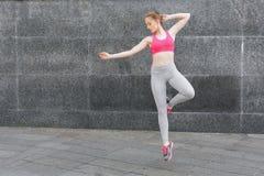 Bella giovane donna che salta contro la parete grigia Immagine Stock