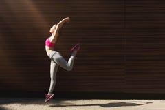 Bella giovane donna che salta contro la parete marrone Immagine Stock