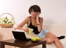 Bella giovane donna che si distende sul sofà con il computer portatile Fotografia Stock Libera da Diritti