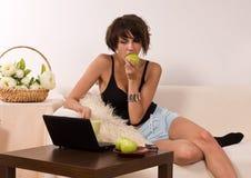 Bella giovane donna che si distende sul sofà con il computer portatile Immagini Stock Libere da Diritti