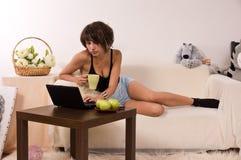 Bella giovane donna che si distende sul sofà con il computer portatile Fotografie Stock Libere da Diritti