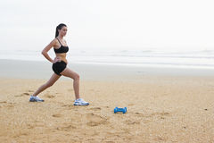 Bella giovane donna che si esercita sulla spiaggia Fotografie Stock Libere da Diritti