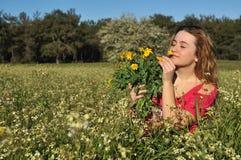 Bella giovane donna che si leva in piedi nel prato di fioritura Fotografia Stock