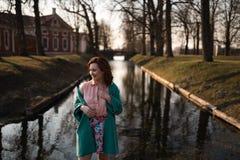 Bella giovane donna che si rilassa vicino ad un fiume del canale in un parco vicino al palazzo in Rundale, Lettonia, 2019 immagine stock libera da diritti