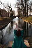 Bella giovane donna che si rilassa vicino ad un fiume del canale in un parco vicino al palazzo in Rundale, Lettonia, 2019 immagini stock