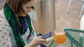 Bella giovane donna che si siede ad una tavola con una birra che scrive un te a macchina immagini stock libere da diritti
