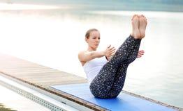 Bella giovane donna che si siede alla sponda del fiume nella posizione di yoga della barca Fotografia Stock