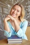 Bella giovane donna che si siede alla tavola con i libri che esaminano macchina fotografica Fotografie Stock