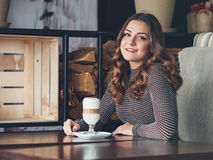 Bella giovane donna che si siede in caffè italiano di stile con la tazza di Fotografia Stock Libera da Diritti