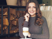 Bella giovane donna che si siede in caffè italiano di stile con la tazza di Immagini Stock Libere da Diritti