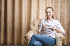Bella giovane donna che si siede con una tazza di tè Fotografia Stock Libera da Diritti