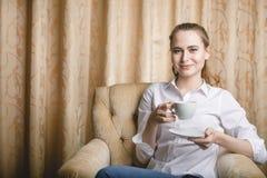 Bella giovane donna che si siede con una tazza di tè Fotografia Stock