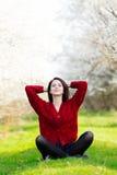 Bella giovane donna che si siede davanti al tre di fioritura meraviglioso Immagini Stock Libere da Diritti
