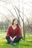 Bella giovane donna che si siede davanti al tre di fioritura meraviglioso Fotografie Stock Libere da Diritti