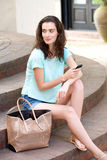 Bella giovane donna che si siede fuori con il telefono cellulare Fotografie Stock Libere da Diritti