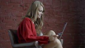 Bella giovane donna che si siede nella sedia e che usando Internet dei wi fi sul suo computer portatile per l'acquisto online video d archivio