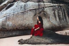 Bella giovane donna che si siede su una pietra sulla spiaggia al tramonto Fotografia Stock Libera da Diritti