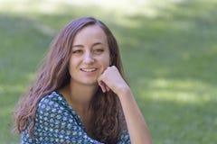 Bella giovane donna che si siede sull'erba Fotografia Stock