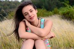 Bella giovane donna che si siede sull'erba asciutta Immagine Stock