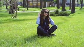 Bella giovane donna che si siede sull'erba nel parco di estate archivi video
