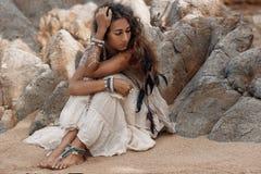 Bella giovane donna che si siede sulla sabbia alla spiaggia Immagini Stock
