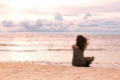 Bella giovane donna che si siede sulla spiaggia al tempo di tramonto Immagine Stock Libera da Diritti