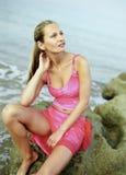 Bella giovane donna che si siede sulle rocce Immagine Stock