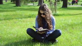 Bella giovane donna che si siede in un parco di estate sull'erba e che legge un libro della bibbia video d archivio