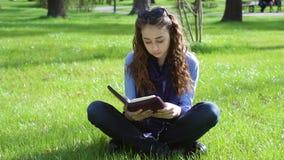 Bella giovane donna che si siede in un parco di estate sull'erba e che legge un libro della bibbia stock footage