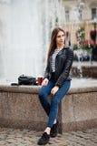 Bella giovane donna che si siede vicino alla fontana sulla via, stile urbano fotografia stock