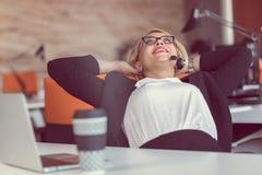 Bella giovane donna che si tiene per mano dietro la testa e che sorride mentre sedendosi al suo posto di lavoro in ufficio fotografia stock libera da diritti