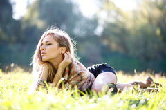 Bella giovane donna che si trova sull'erba Immagini Stock Libere da Diritti