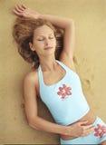 Bella giovane donna che si trova sulla sabbia Immagini Stock