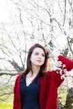 Bella giovane donna che sta davanti al TR di fioritura meraviglioso Immagini Stock