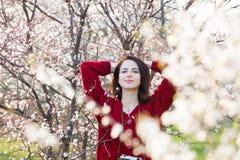 Bella giovane donna che sta davanti al TR di fioritura meraviglioso Immagine Stock