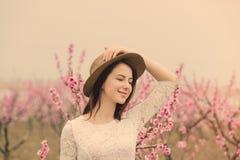 Bella giovane donna che sta davanti al TR di fioritura meraviglioso Fotografia Stock