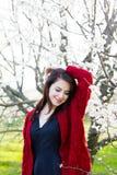 Bella giovane donna che sta davanti al TR di fioritura meraviglioso Immagini Stock Libere da Diritti