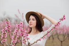 Bella giovane donna che sta davanti al TR di fioritura meraviglioso Immagine Stock Libera da Diritti