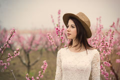 Bella giovane donna che sta davanti al TR di fioritura meraviglioso Fotografie Stock Libere da Diritti