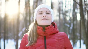 Bella giovane donna che sta in un parco di inverno, sorridere, prendente una respirazione profonda video di movimento lento stock footage