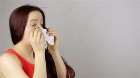 Bella giovane donna che starnutisce in un fazzoletto video d archivio