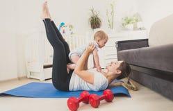 Bella giovane donna che tiene il suo neonato e che si esercita sul pavimento a casa Fotografia Stock