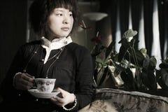 Bella giovane donna che tiene una tazza della bevanda calda Immagine Stock