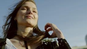 Bella giovane donna che tocca i suoi capelli e che flirta video d archivio