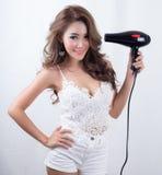 Bella giovane donna che usando il ventilatore dei capelli fotografie stock