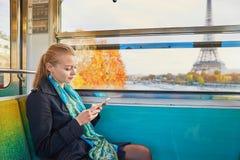Bella giovane donna che viaggia in un treno del parigino nel sottosuolo e che per mezzo del suo telefono cellulare Fotografia Stock Libera da Diritti
