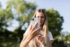 Bella giovane donna con capelli biondi facendo uso del telefono cellulare all'aperto Ragazza alla moda che fa selfie immagini stock libere da diritti