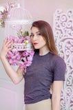 Bella giovane donna con capelli biondi lunghi, occhi azzurri, gabbia di fioritura, maglietta d'uso Immagine Stock Libera da Diritti
