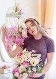 Bella giovane donna con capelli biondi lunghi, occhi azzurri, gabbia di fioritura, maglietta d'uso Immagini Stock