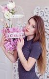 Bella giovane donna con capelli biondi lunghi, occhi azzurri, gabbia di fioritura, maglietta d'uso Immagine Stock